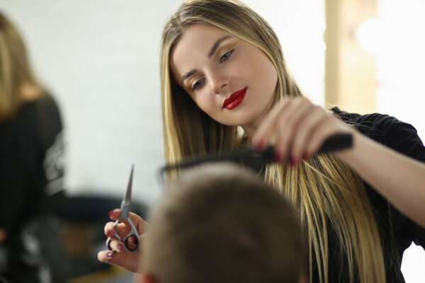 Young Woman Barber Cutting Client Hair in Salon. Hairdresser Holding Scissors and Hairbrush. Beautiful Hairstylist Combing Man. Beautician Styling Male Haircut in Beauty Salon. Professional Barbershop